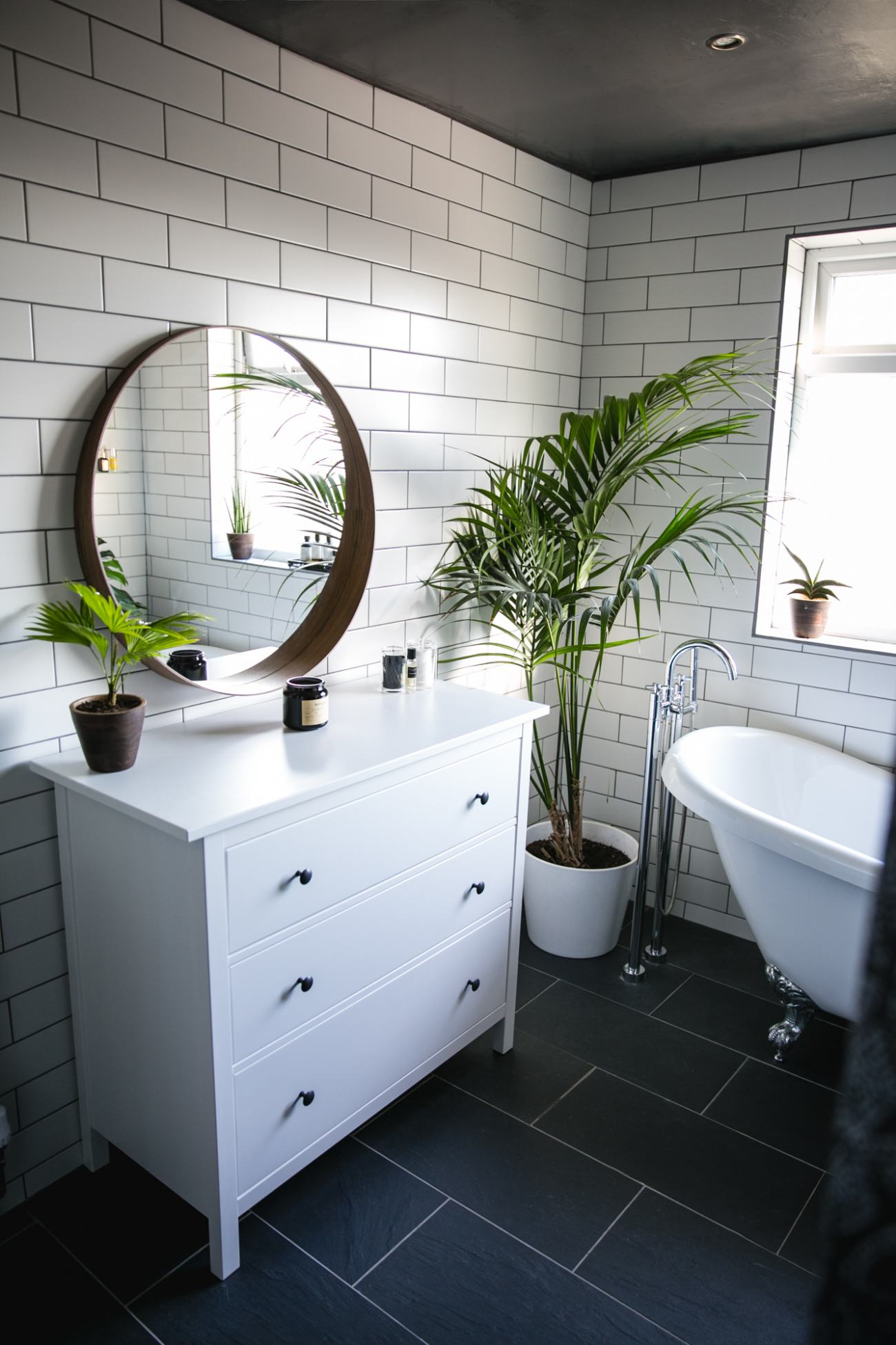 white tiles grey grout, roll top bath, palm plant, round wall mirror, slate floor, round mirror, bathroom design