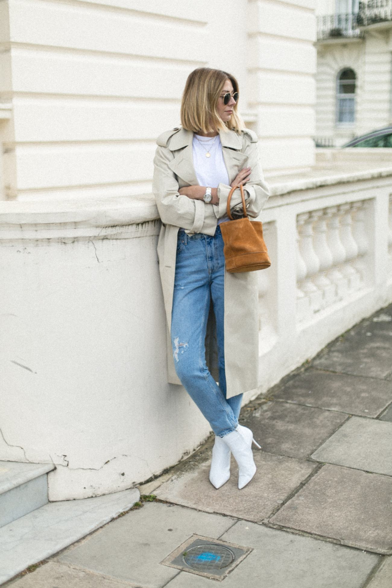 Emma Hill wearing Trench coat, light wash jeans, white ankle boots, Simon Miller tan nubuck Bonsai bucket bag, chic Spring outfit