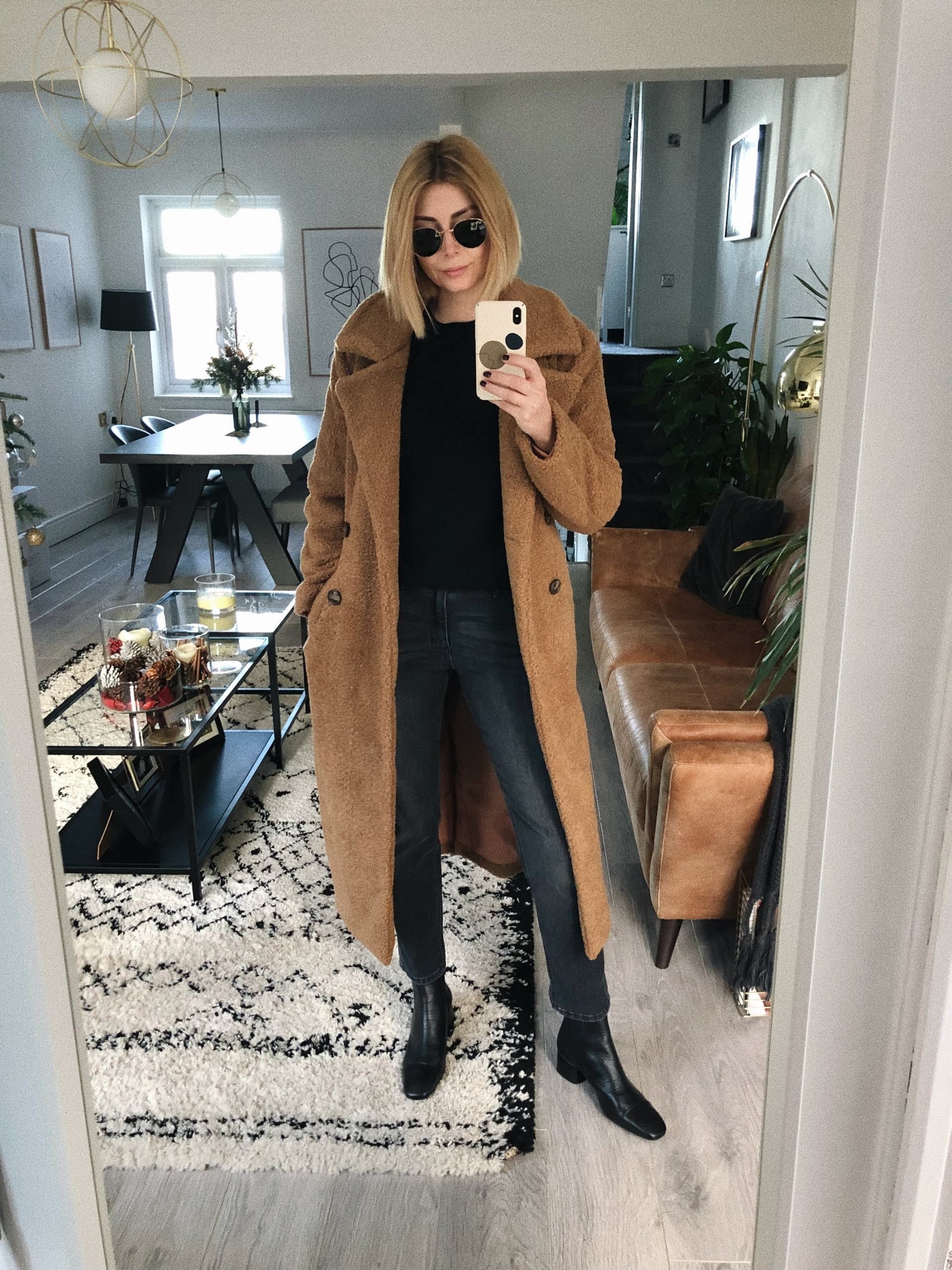 Emma Hill wears brown teddy coat, black jeans, black cashmere jumper, black ank;le boots, round sunglasses, chic casual winter outfit