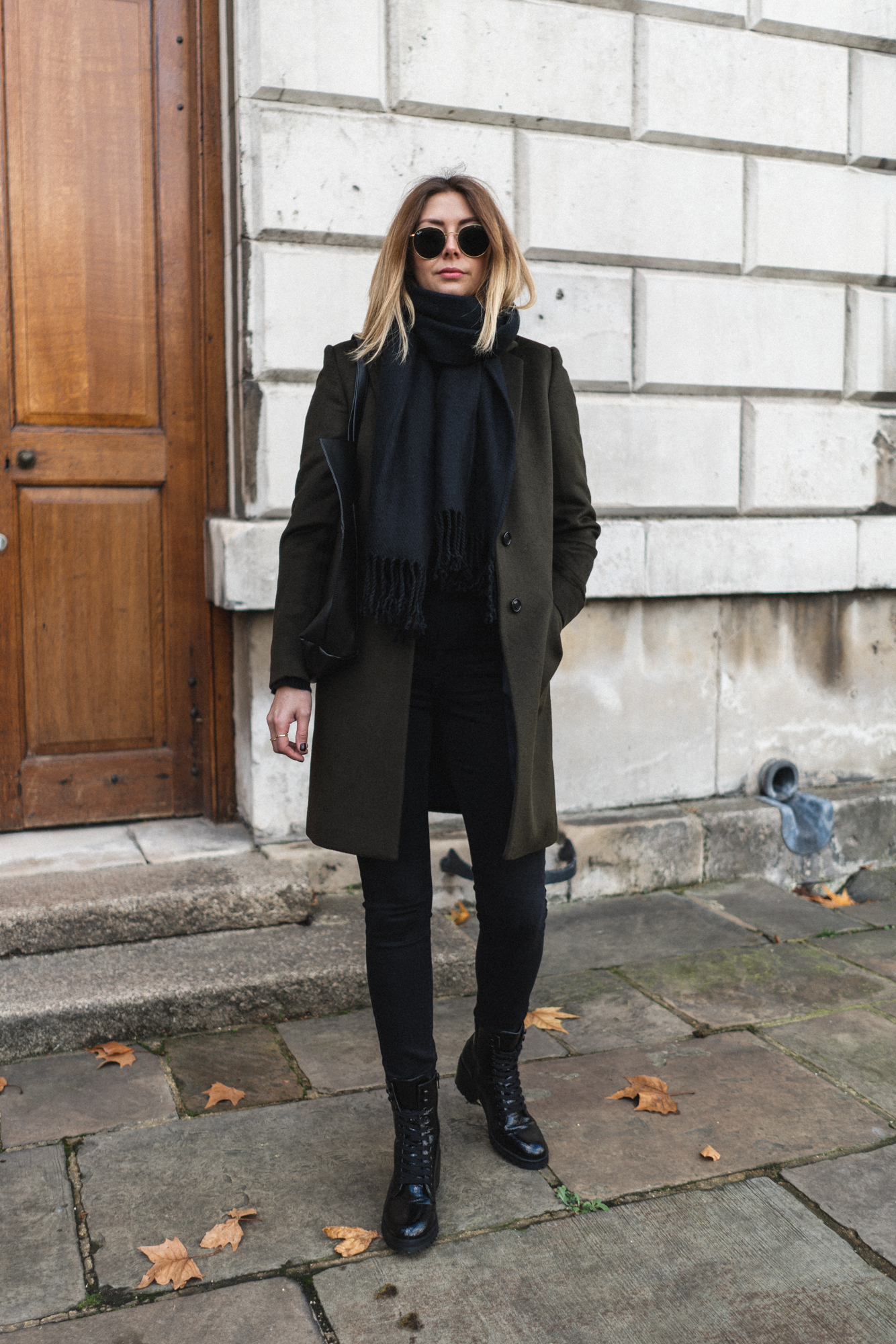 Emma Hill wears dark green wool coat, black scarf, skinny jeans, lace up boots, chic winter outfit