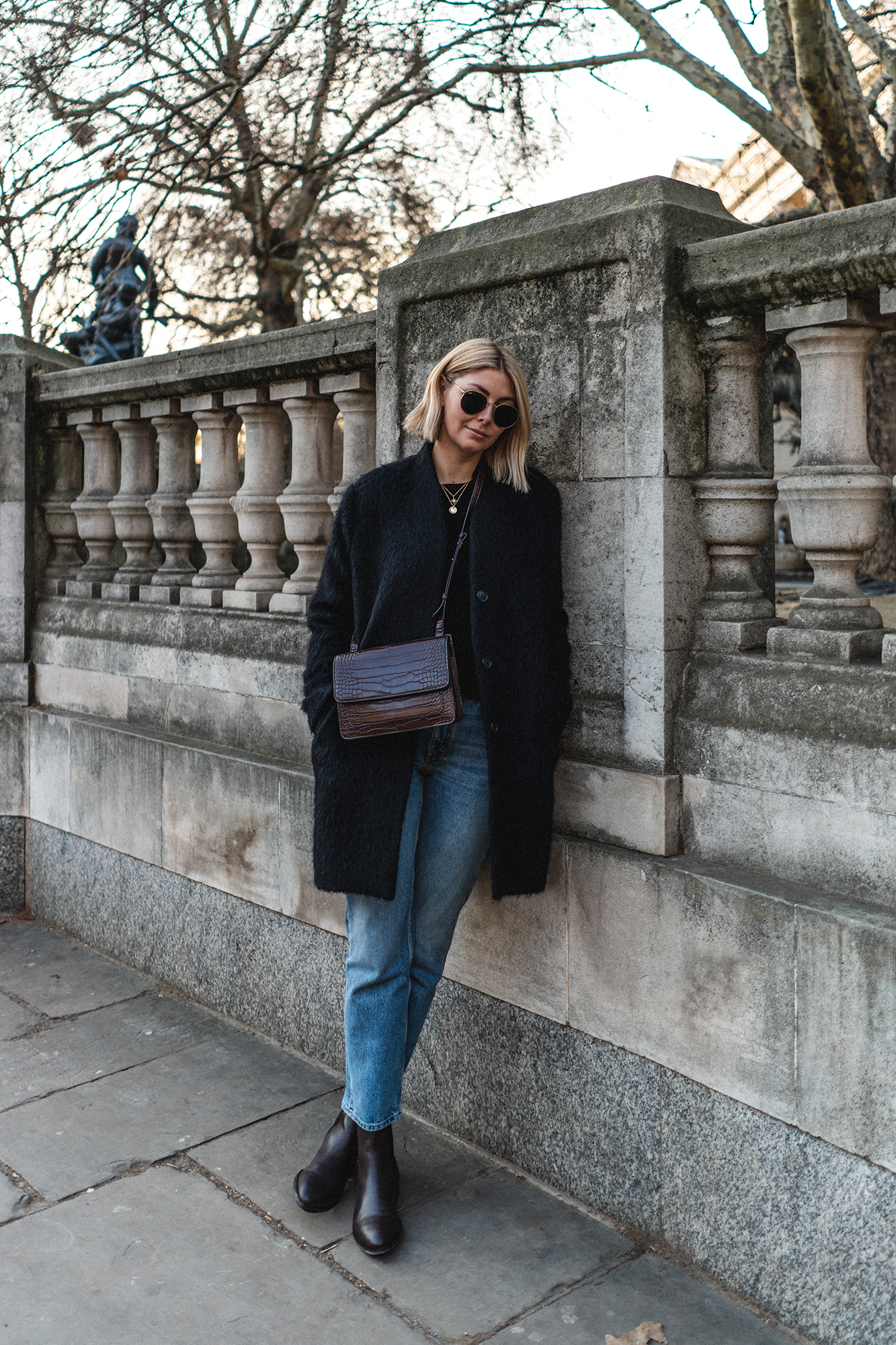 Black coat, brown croc crossbody bag, chelsea boots and mid wash jeans