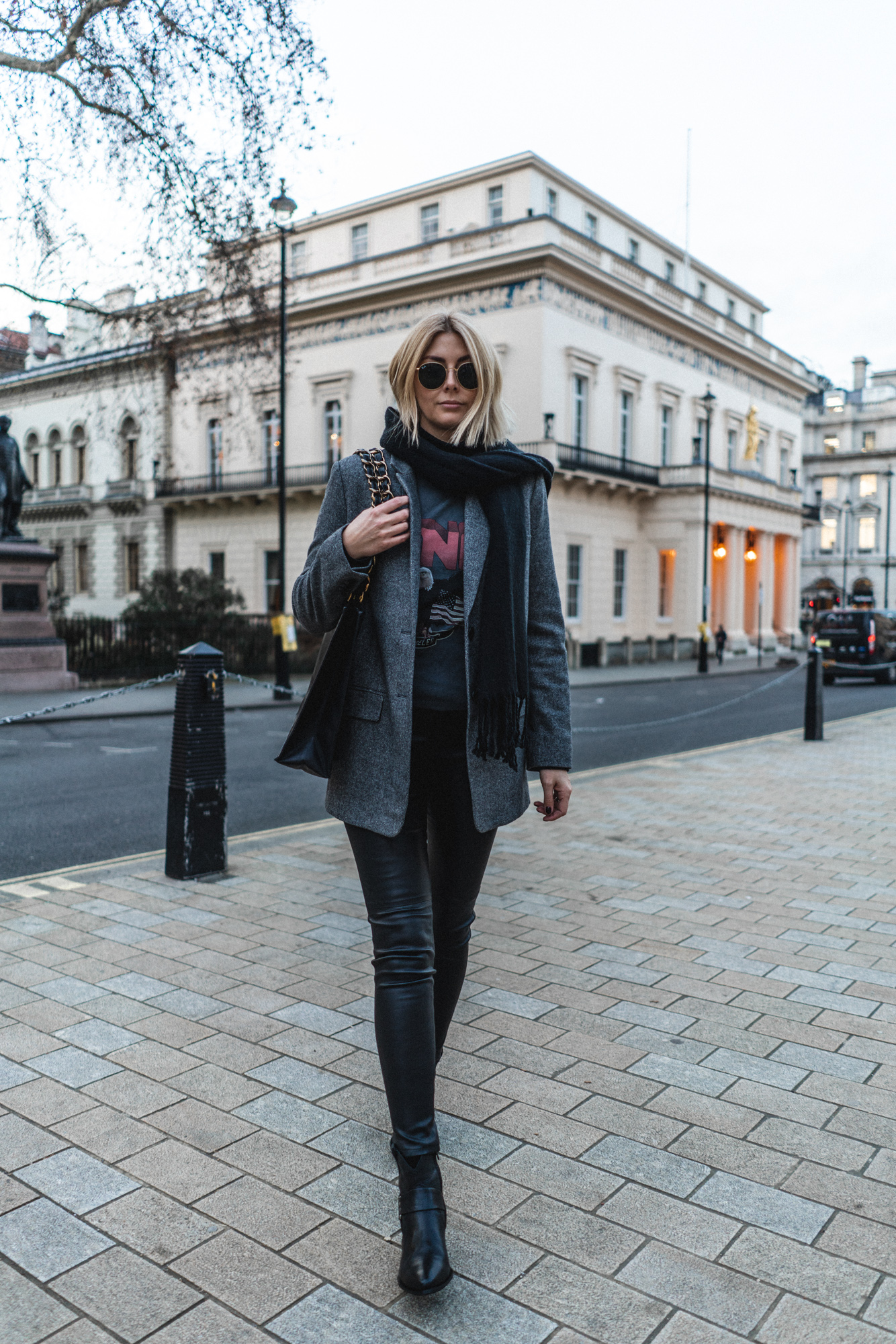 Emma Hill wears leather trousers, grey tweed blazer, anine bing t-shirt, western boots, black scarf, winter outfit
