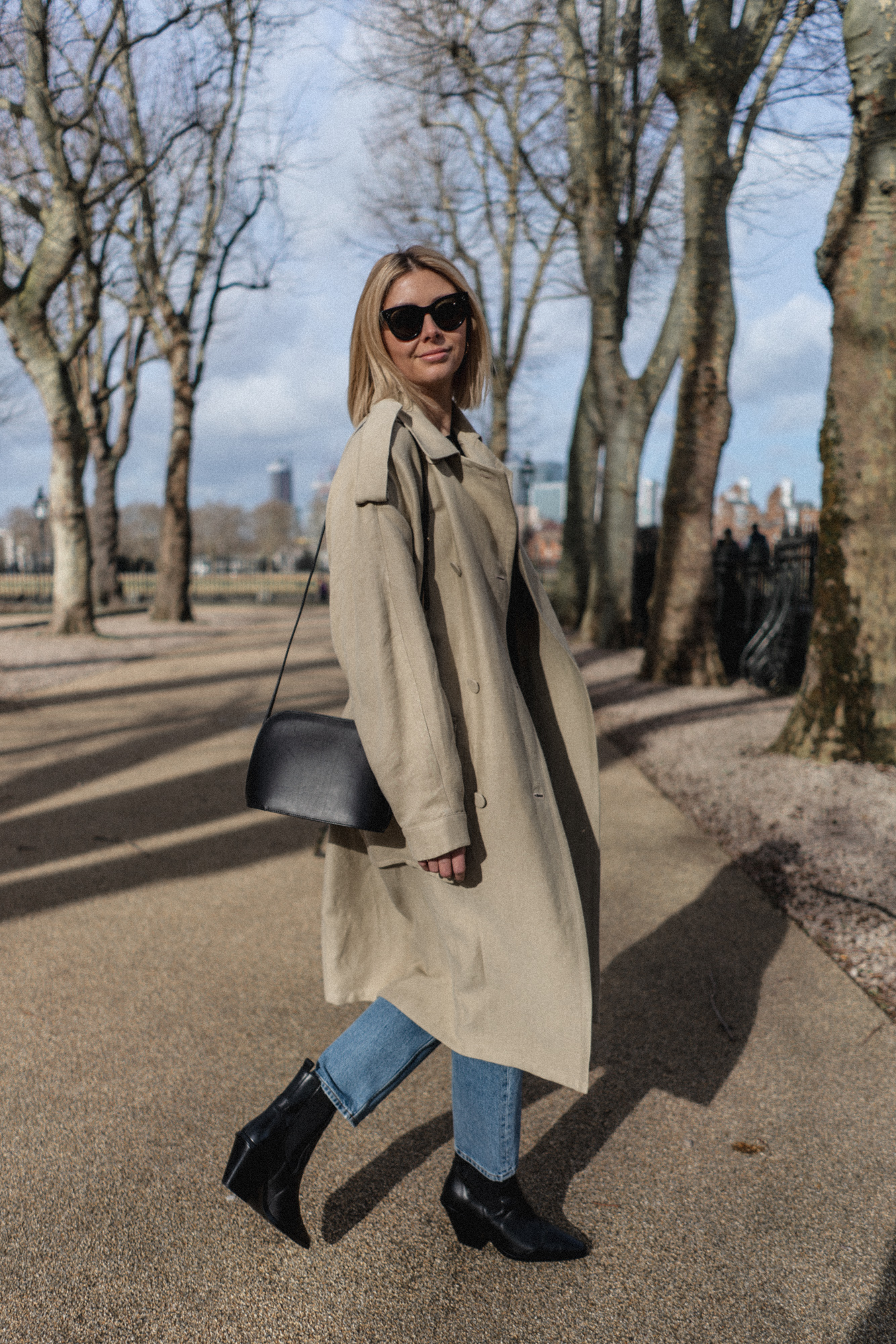 Emma Hill style. Beige linen trench coat, light wash striaght leg jeans, black western cowboy boots, black shoulder bag, Celine baby Audrey sunglasses, chic Spring outfit
