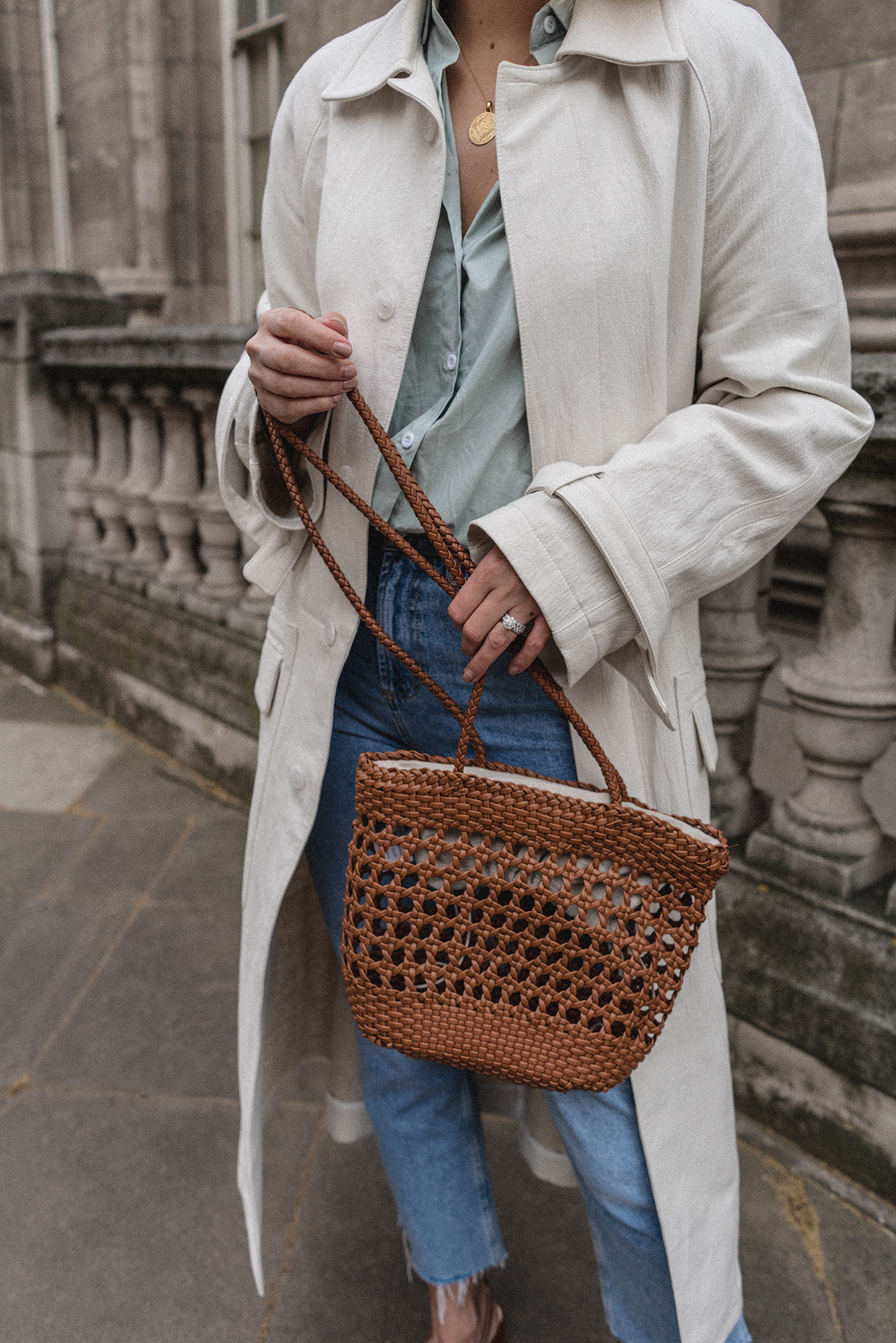 Emma Hill style, off white duster trench coat, wint green shirt, light wash jeans, tan leather woven bag, gold mini marie necklace, Spring outfit