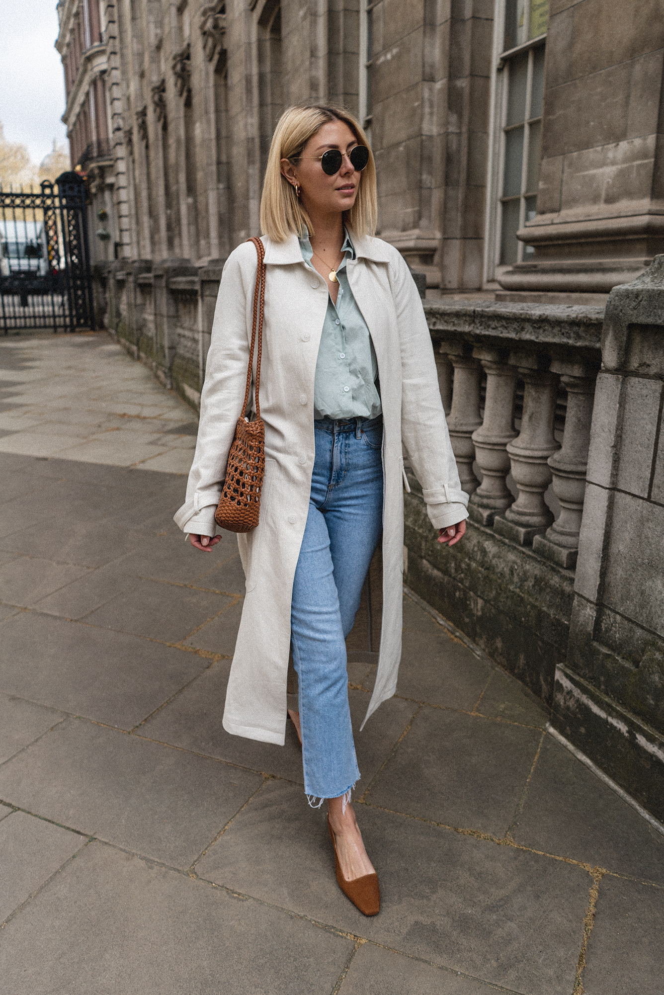 Emma Hill style, off white duster trench coat, wint green shirt, light wash jeans, tan leather woven bag, gold mini marie necklace, Tan suede slingback shoes, Spring outfit