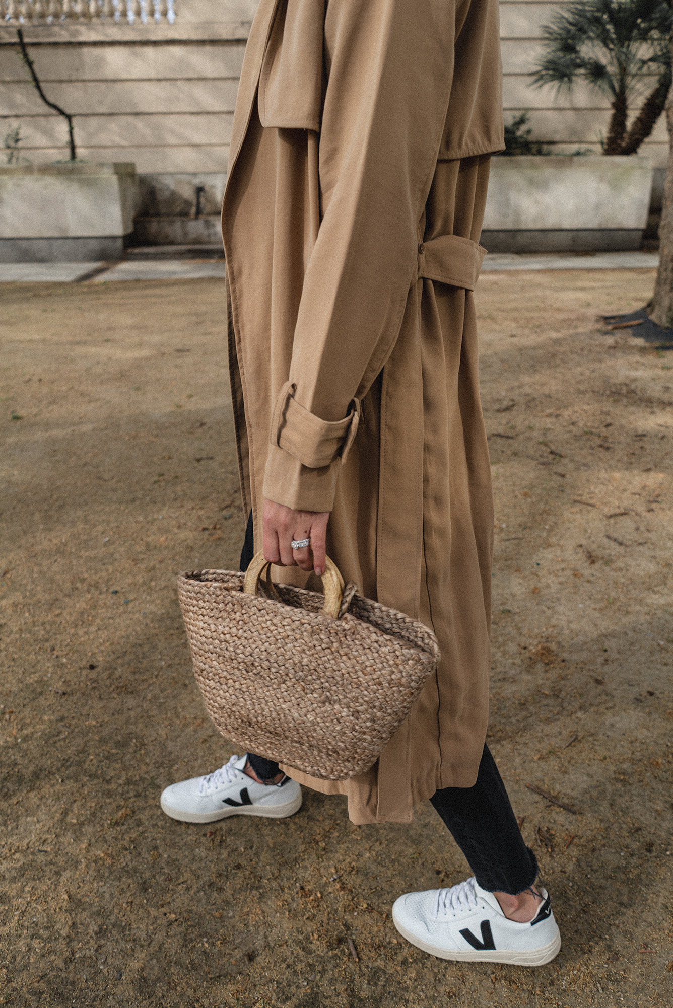 Straw bag with wooden handles, tan trench coat, black raw hem jeans, Veja V-10 trainers