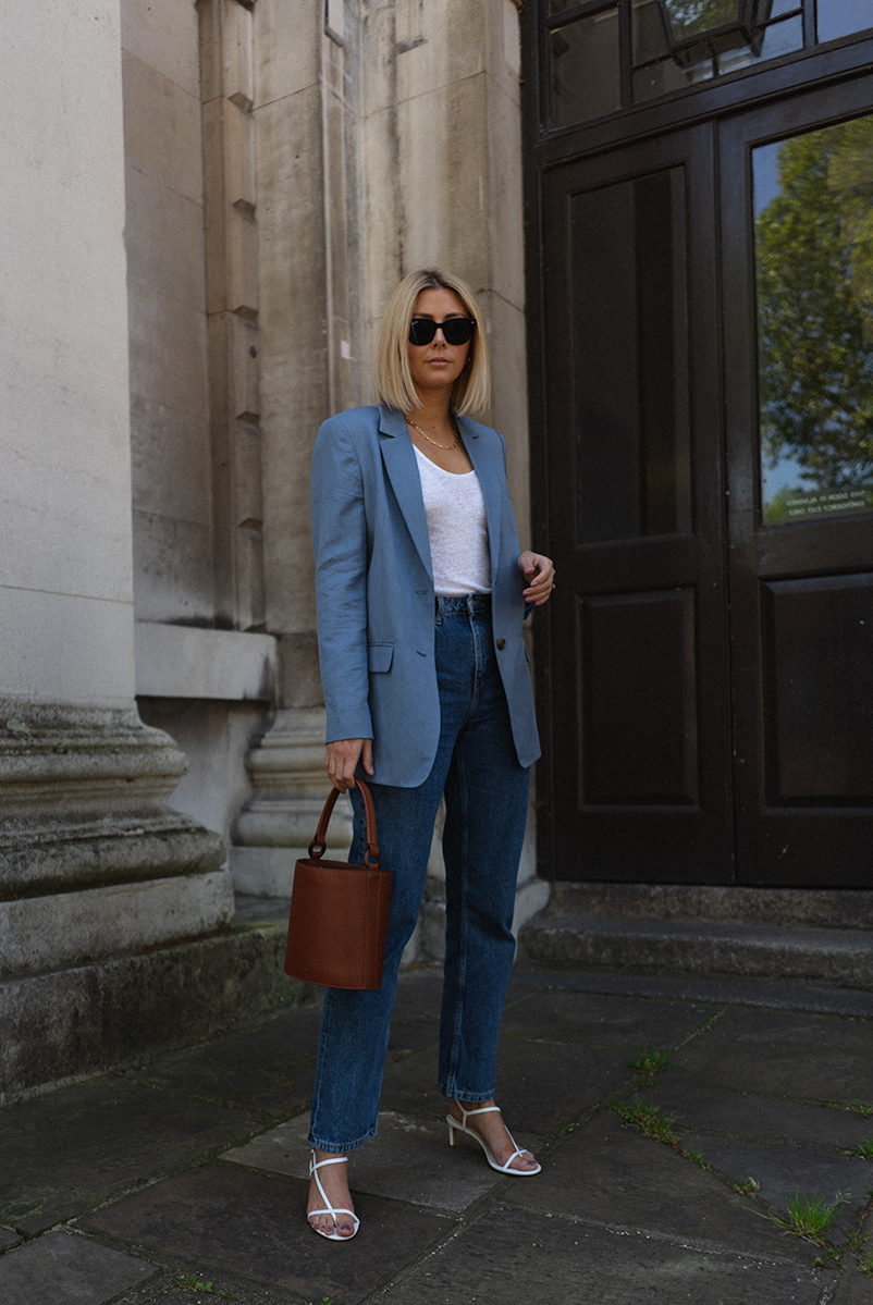 Emma Hill style, black Ray Bay sunglasses, blue linen blazer, white linen vest top, brown tan leather bucket bag, straight leg jeans, white strappy sandals, chic spring summer outfit