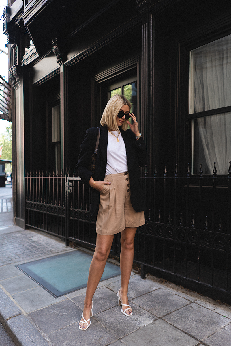 Emma Hill, white strappy sandals, long tan shorts, black blazer, white t-shirt, layered gold necklaces, vintage Fendi baguette bag, chic Summer style