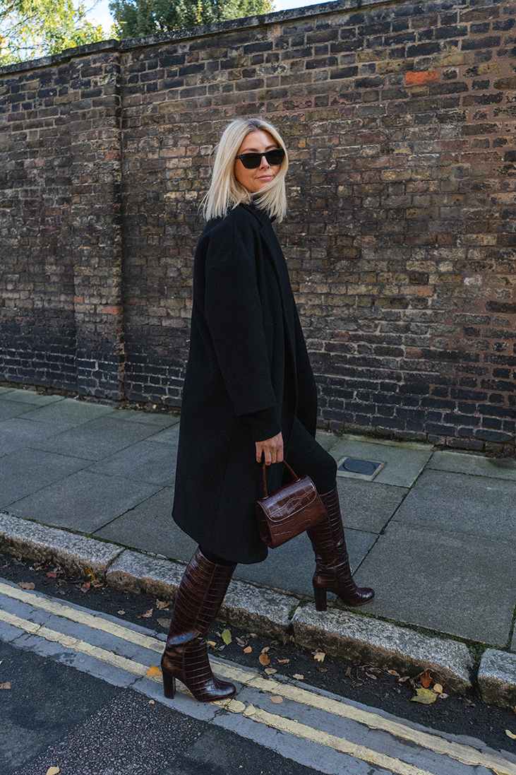 Emma Hill style. Black oversized wool coat, Le Specs sunglasses, By Far mini bag, brown mock croc knee high boots, black skinny jeans, black jumper, chic autumn winter outfit
