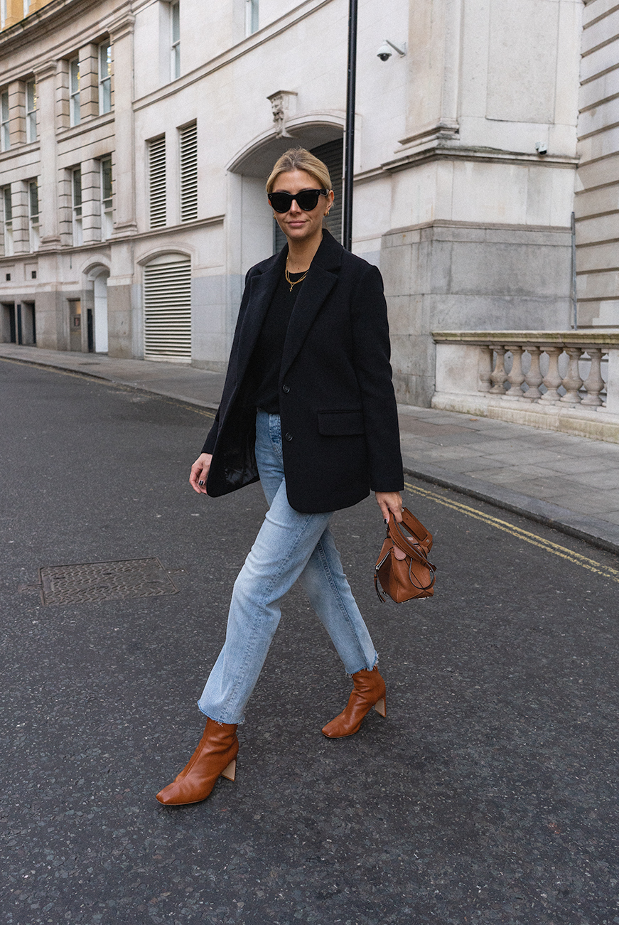 Emma Hill style. Black wool blazer, black basic jumper, light wash raw hem straight leg jeans, tan leather square toe boots, Loewe Puzzle bag, Céline Baby Audrey sunglasses, chic autumn fall outfit