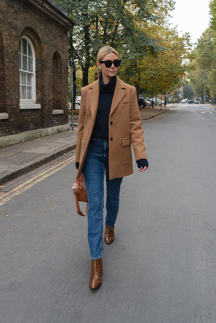 Emma Hill style. Camel wool blazer, navy high neck jumper, straight leg jeans, tan mock crock ankle boots, tan Loewe Puzzle bag, chic autumn fall outfit