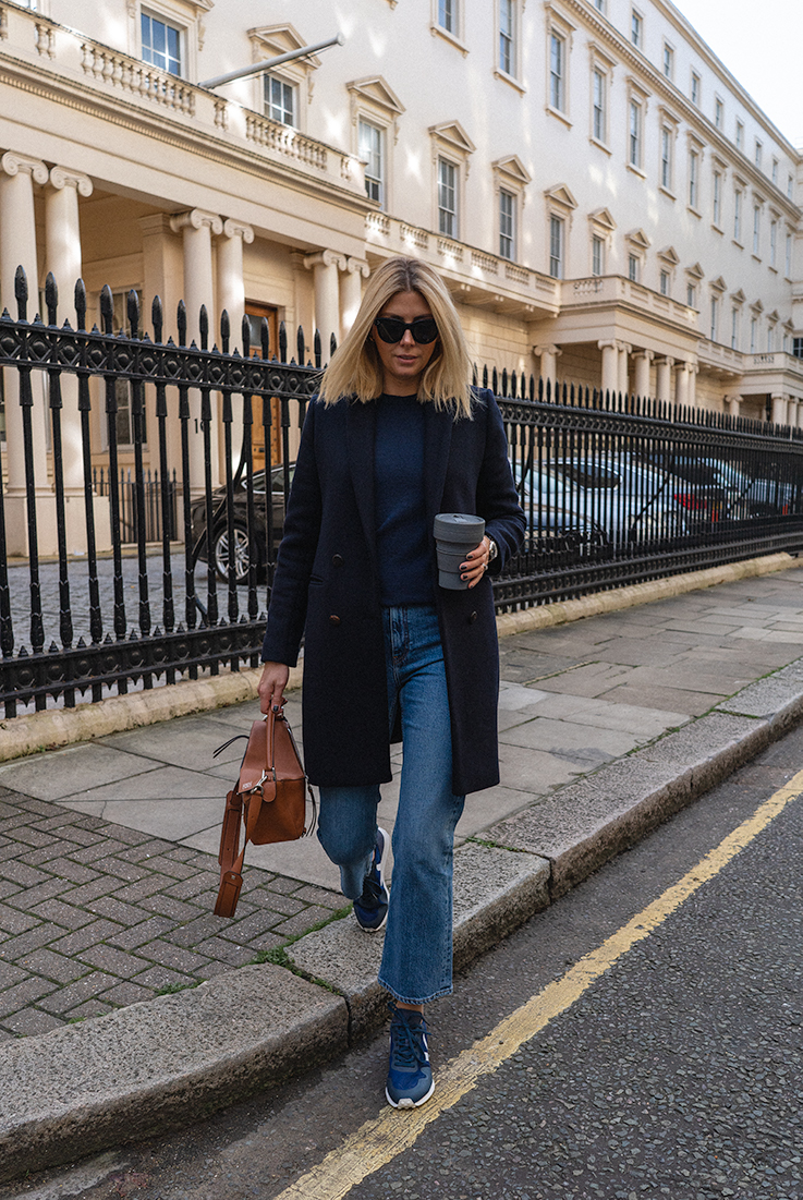 Emma Hill style. Casual Autumn weekend outfit. Navy wool coat, navy cashmere jumper, cropped kick flare jeans, blue Veja runner trainers, tan leather Loewe puzzle bag, Celine baby audrey sunglasses