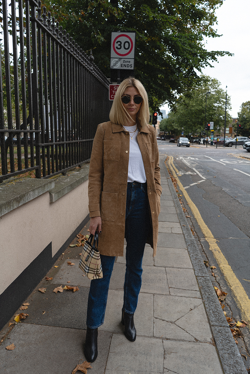 Emma Hill style. Tan suede Mango coat, white t-shirt, gold Missoma necklaces, high waisted straight legs jeans, Dear Framces Spirit boots, vintage Burberry check mini tote bag. Chic Autumn Fall outfit