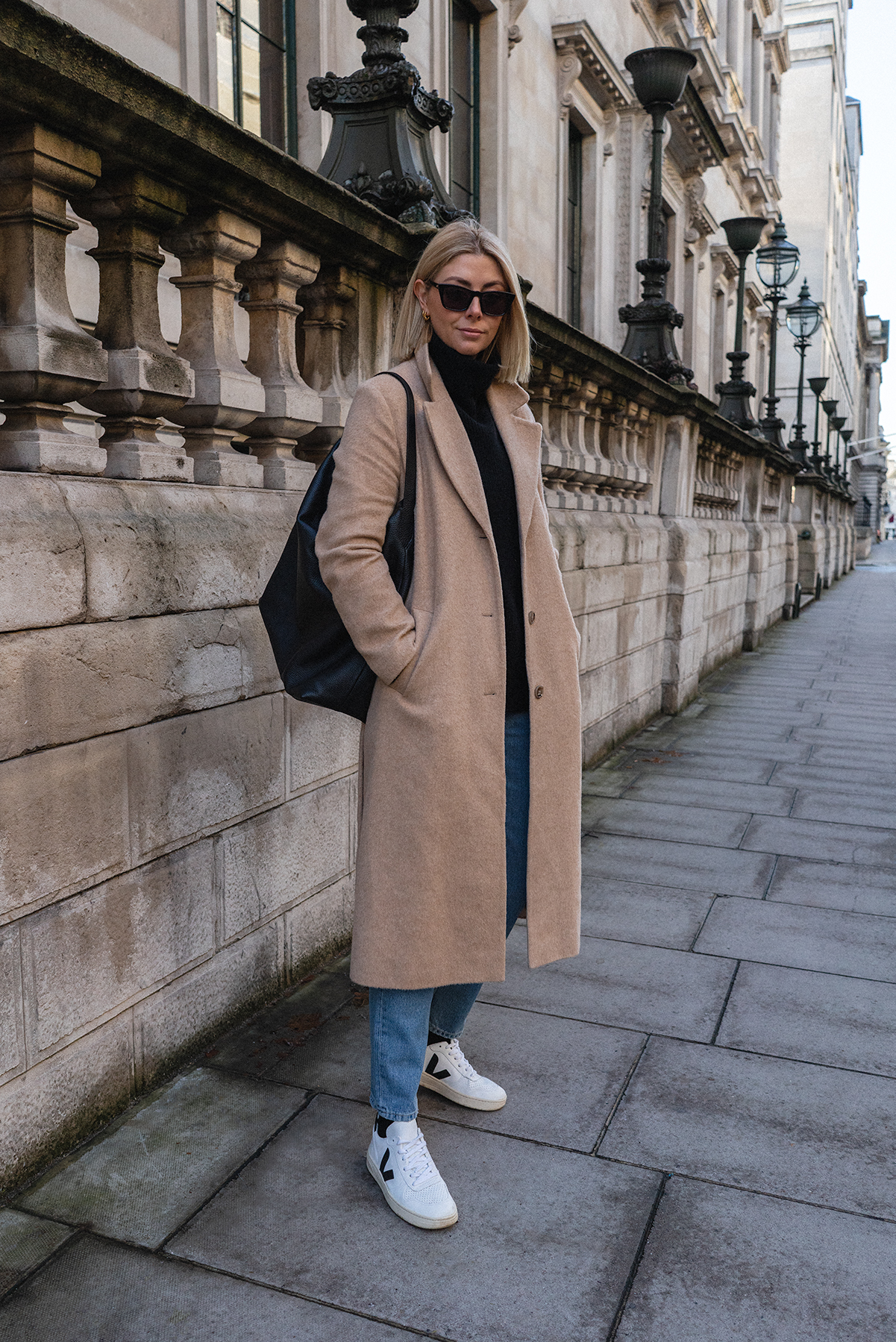 Emma Hill style, camel coat, light wash jeans, black socks, Veja V-10 white trainers, black leather Everlane hobo bag, Le Specs sunglasses, casual autumn winter outfit