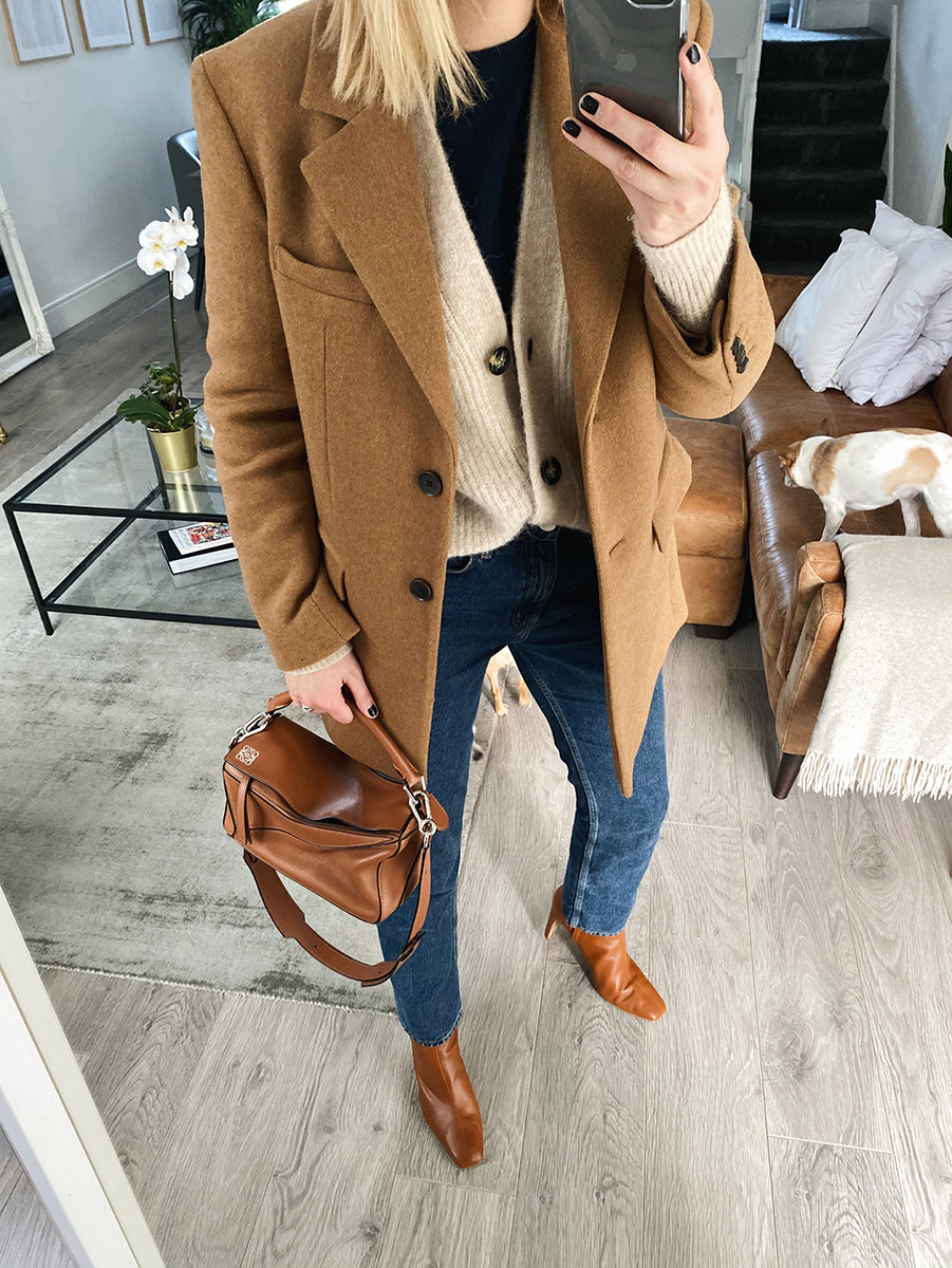 Emma Hill style. Camel wool blazer, beige cardigan, navy cashmere jumper, straight leg jeans, tan leather ankle boots, tan Loewe Puzzle bag. Autumn layers. Chic outfit_