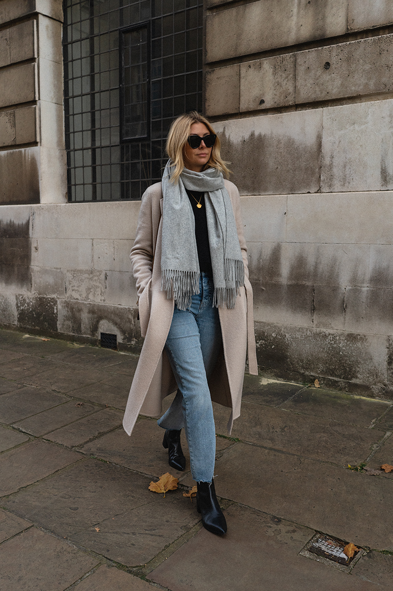 Emma Hill style. Cream belted Winter coat, grey cashmere scarf, black jumper, raw hem straight jeans, Everlane Boss black ankle boots, Celine Baby Audrey sunglasses