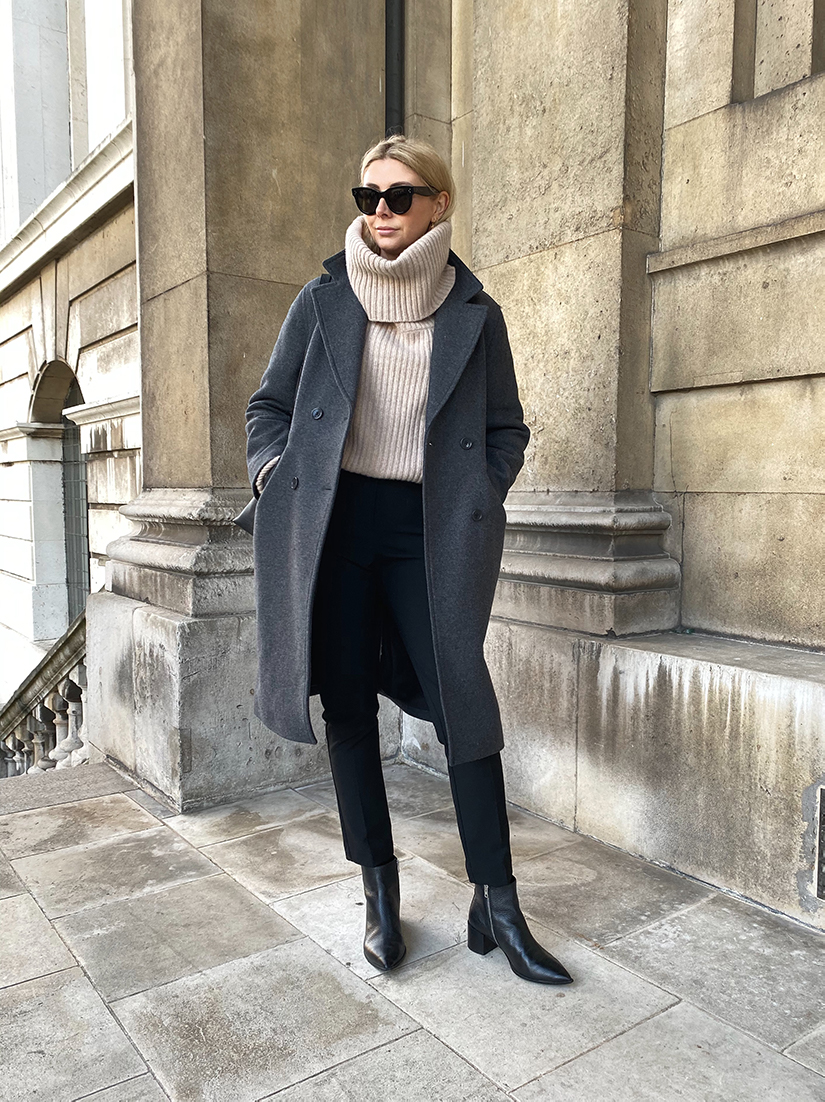 Emma Hill wears grey wool coat, beige chunky neck jumper, black skinny trousers, Everlane Boss boots, black ankle boots, chic winter workwear outfit