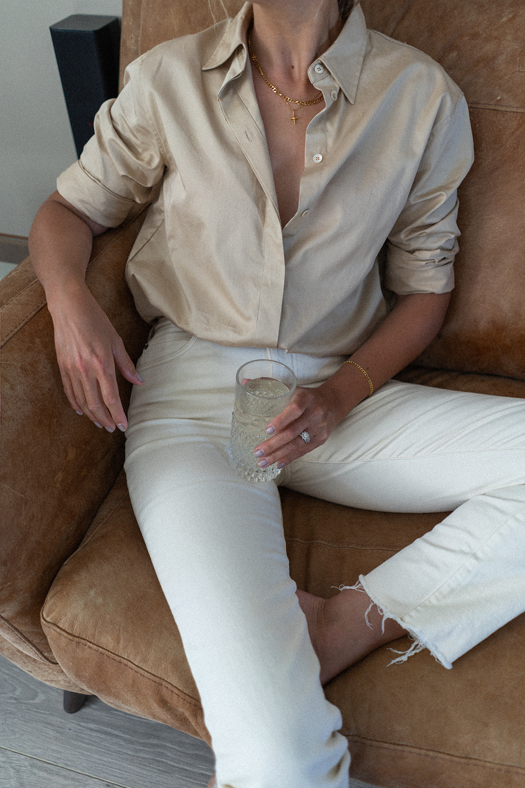 Emma Hill style and home. Beige shirt, gold jewellery, ecru jeans, mid century modern interiors, tan leather sofa