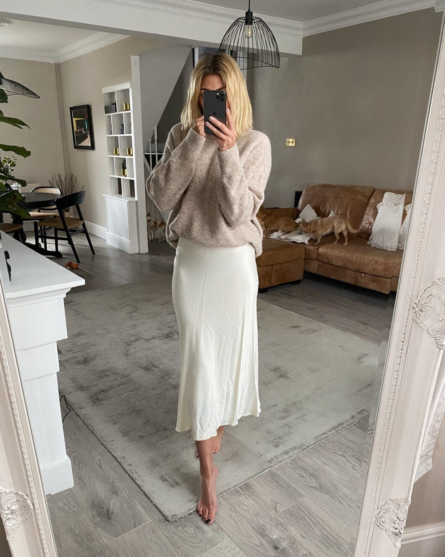 Emma hill wears beige jumper, ivory satin slip skirt, dress up fridays at home