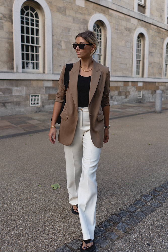 Emma Hill style. Camel blazer, black vest top, Celine Seau Sangle black leather bucket bag, white wide leg tailored trousers, black leather thong sandals, chic Spring Summer outfit blog