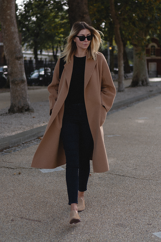 Emma Hill Autumn style. Camel cashmere wool blend coat, Celine black Seau Sangle bag, Ray-ban Meteor sunglasses, beige suede loafers, black cashmere sweater, black jeans. Autumn winter outfit inspiration