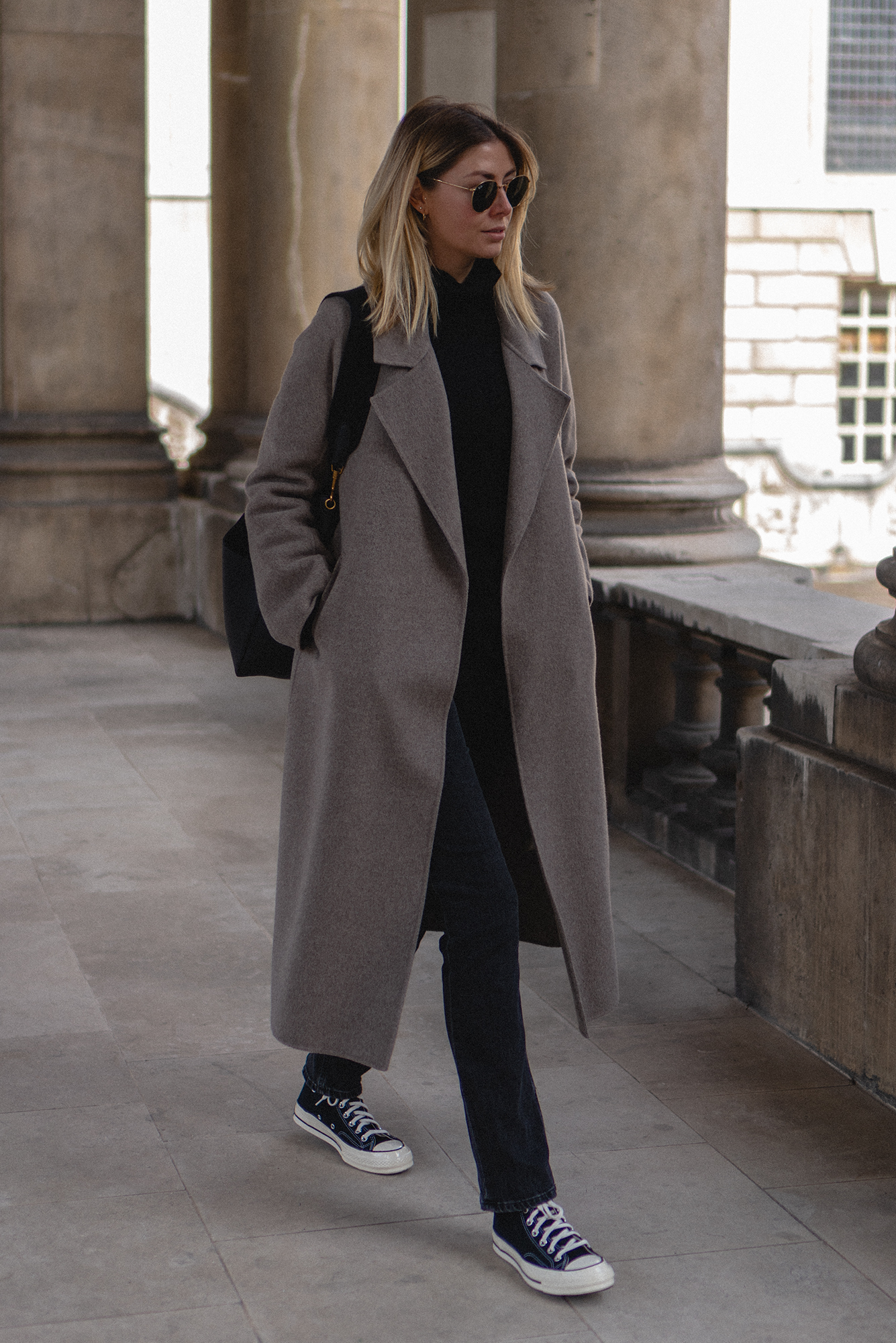 Emma Hill Fall style. Taupe cashmere wool blend coat, Converse Chuck 70, black leather Celine Seau Sangle bag, black jumper, Ray-Ban round metal gold sunglasses. Chic Autumn Winter outfit
