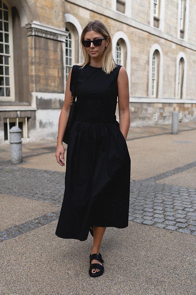 Emma Hill casual summer style. Black sleeveless midi dress with pockets, black leather dad sandals, gold anklet, Celine seau sangle bag