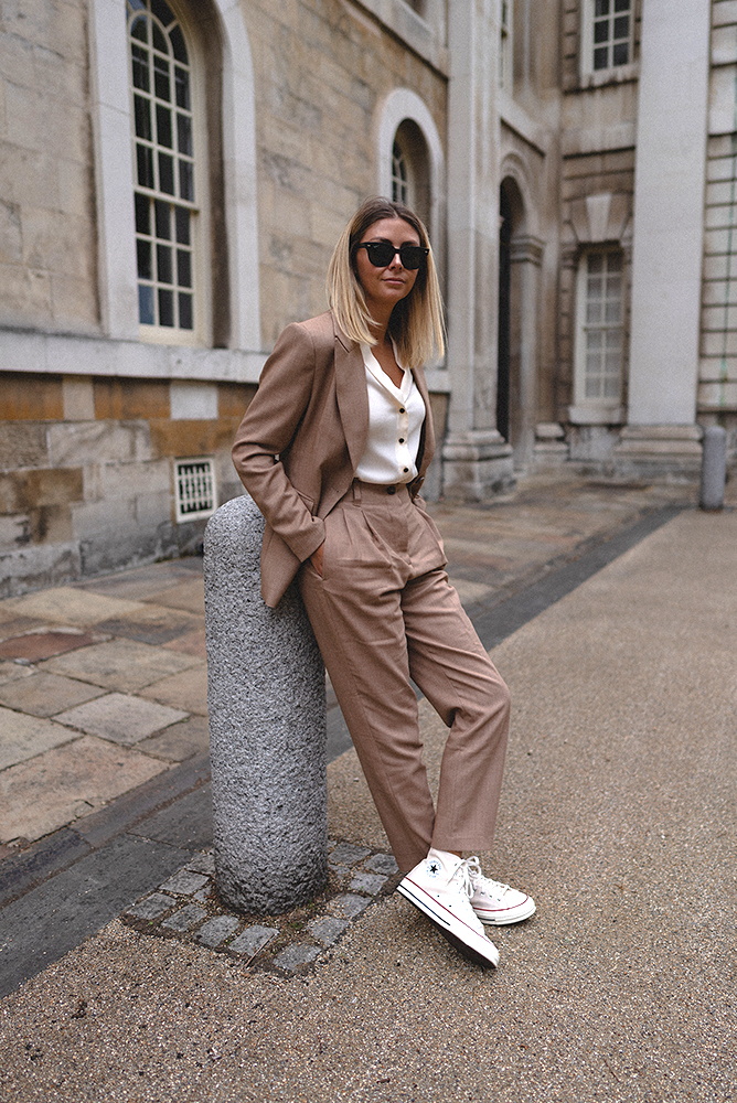 Emma Hill style. Camel tailored suit, cream shirt, rayban meteor sunglasses, cream parchment converse chuck 70 trainers