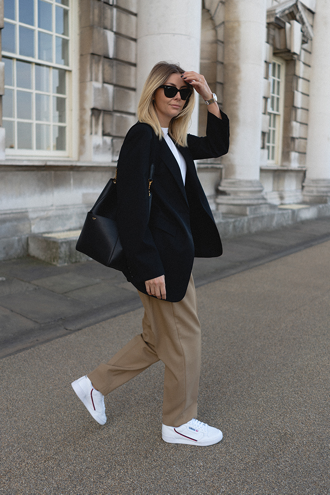 Emma Hill style. Transitional outfit Autumn style. Black blazer, camel tailored trousers, white trainers, Celine Seau Sangle bag