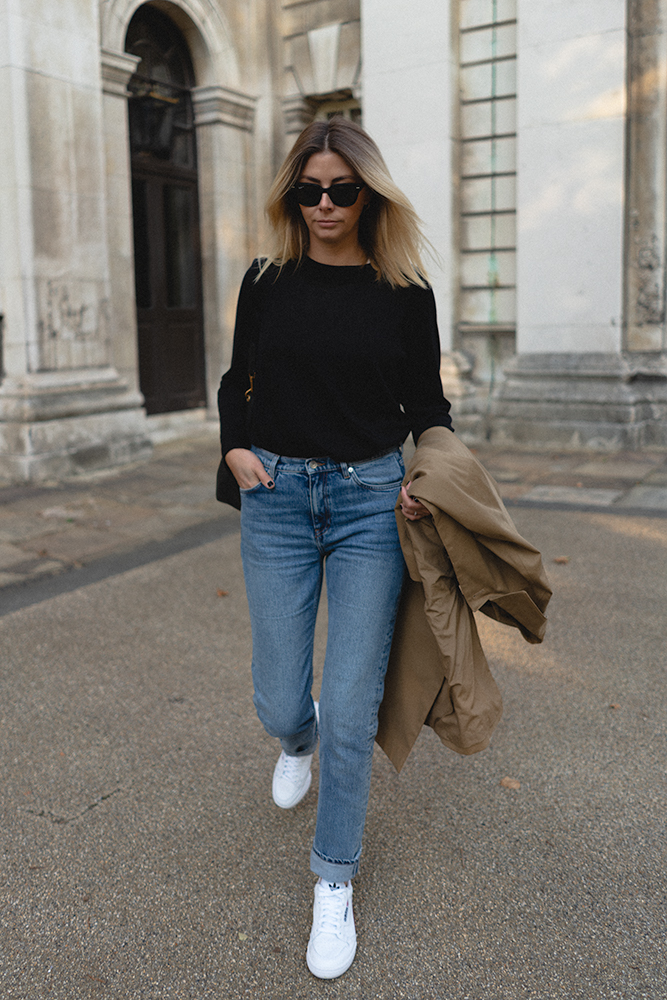Emma Hill style. Transitional outfit ideas, autumn fall style. Mid wash straight leg jeans, trench coat, black jumper, white Adidas original trainers, Celine Sea Sangle bag