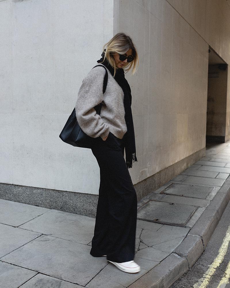 Emma Hill Autumn style. Beige chunky knit jumper, black Acne Canada scarf, black wide leg trousers, Celine Seau Sangle bag, Converse Chuck 70 in cream. Casual Autumn outfit