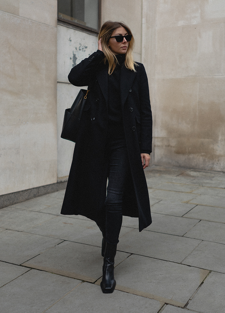 Emma Hill Autumn style. Black tailored wool long coat, black square toe ankle boots, skinny jeans, high neck jumper. All black outfit. Autumn Winter outfit