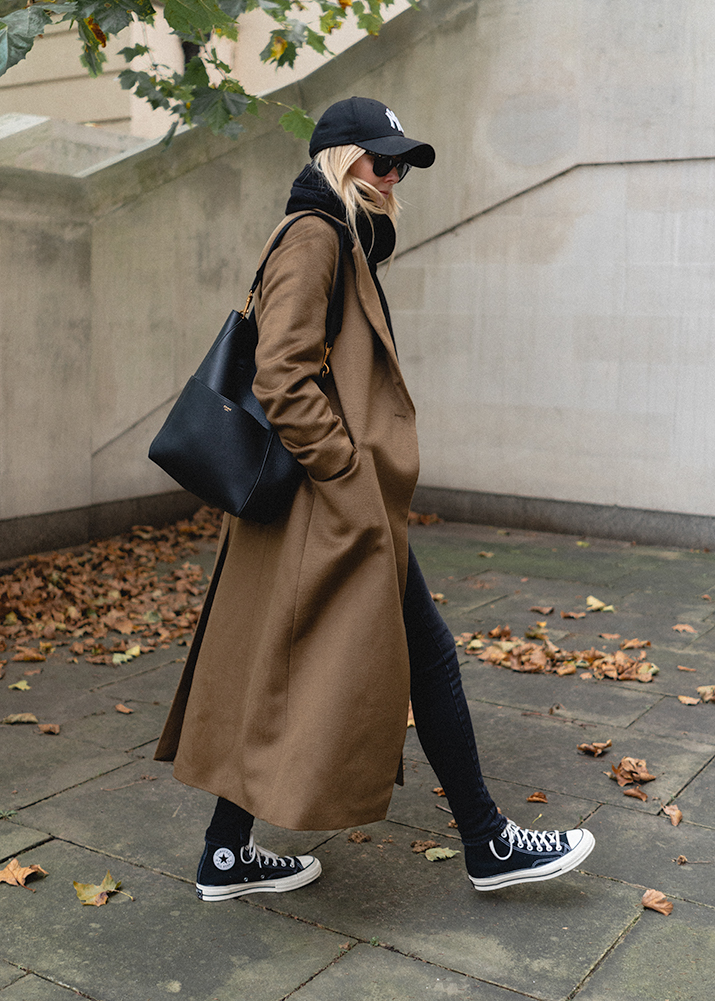 Emma Hill Autumn style. Long green wool coat, black skinny jeans, Converse high top sneakers, NY Yankee baseball cap hat, Celine Seau Sangle. Off duty casual weekend Autumn Winter outfit