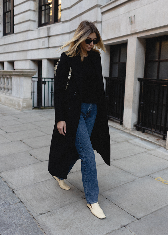 Emma Hill Autumn style. Long tailored black coat, dark wash straight leg jeans, black cashmere crew neck jumper, cream square toe loafers, By Far snakeskin Rachel bag. Chic Autumn outfit