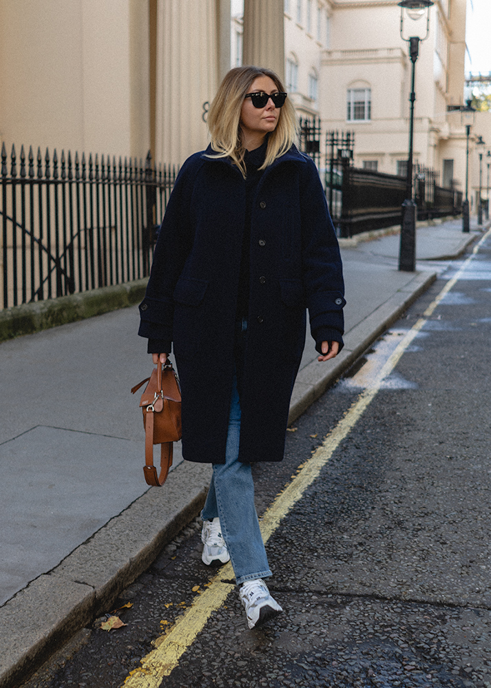 Emma Hill Autumn style. Navy blue wool coat, straight leg jeans, New Balance 530 trainers, tan leather Loewe Puzzle bag. Casual autumn winter outfit ideas