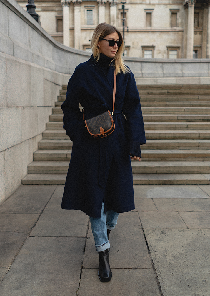 Emma Hill Autumn style. Navy blue wrap coat, Celine Triomphe camvas crossbody Folco bag, Light wash turn up jeans, square toe black ankle boots. Autumn outfit ideas
