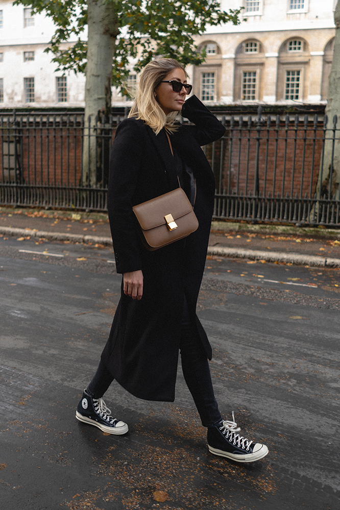 Emma Hill style. Black double breasted long wool coat, camel Celine Classic bag, black skinny jeans, Converse high tops, all black outfit. Chic Autumn outfit