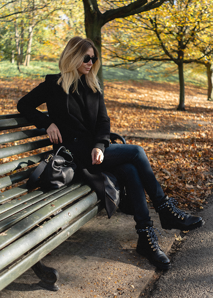 Emma Hill Fall style. Autumn outfit, black wool coat, black leather chunky lace up hiking boots, dark blue skinny jeans, black Elleme bag