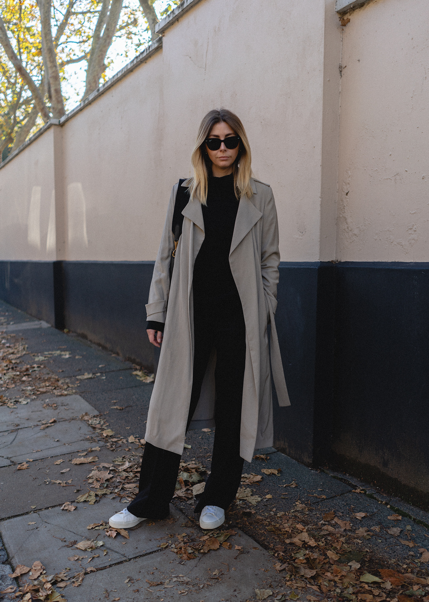 Emma Hill style. Beige belted trench coat, black wide leg trousers, black cashmere high neck jumper, Veja Campo trainers. Chic casual Autumn outfit