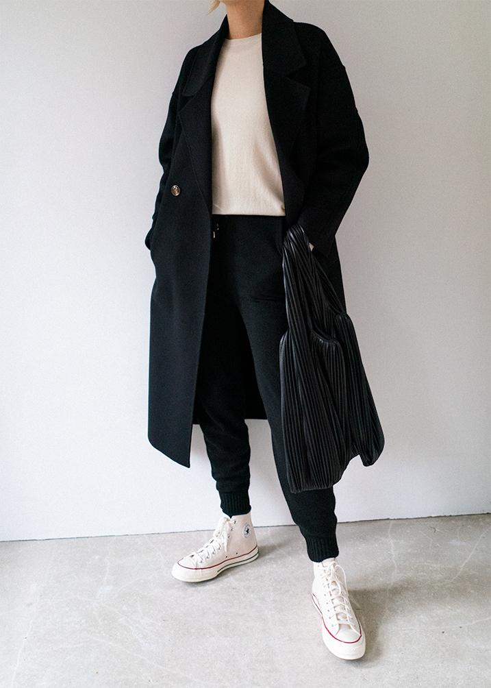 Black cashmere joggers track pants, Converse Cuck 70 high top trainers, cream cashmere jumper, black wool coat, Nanushka Jo vegan leather shopper bag