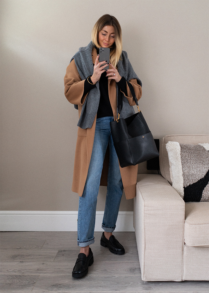 Camel cashmere coat, grey jumper worn over shoulders, black jumper, mid wash straight leg jeans, black chunky loafers, Celine Seau Sangle bag. Chic casual Autumn Winter outfit idea