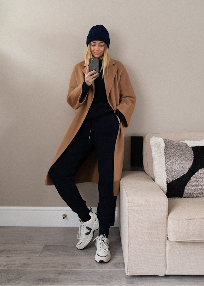Camel coat, navy wool beanie hat, navy cashmere joggers, navy roll neck jumper, Veja Venturi chunky trainers. Casual Winter outfit ideas