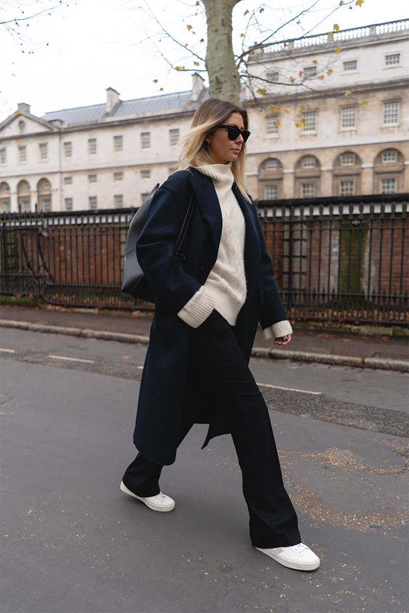 Emma Hill style, navy coat, black wool flare leg trousers, Wander Ava bag, Veja trainers, cream cable knit jumper. Chic minimalist normcore Winter outfit_