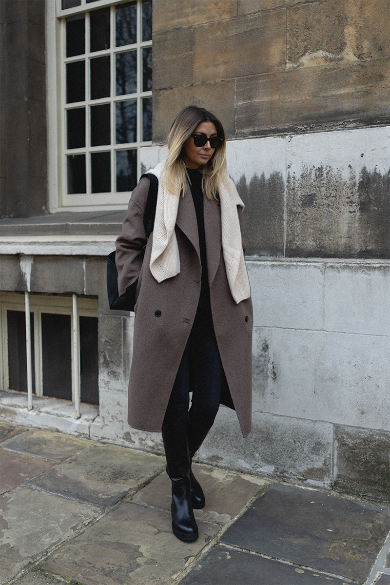Emma Hill style, taupe wool coat, cream cashmere jumper worn over shoulders, washed black jeans, black knee high chunly boots