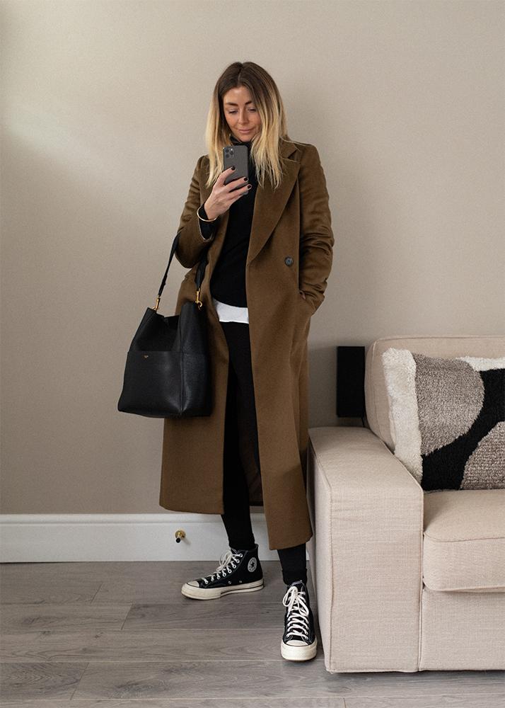 Olive green wool long coat, black Celine Seau Sangle bag, black leggings, black cashmere jumper, white shirt, gold bangle, black Converse chuck 70 high tops. Layered Autumn Winter outfit idea