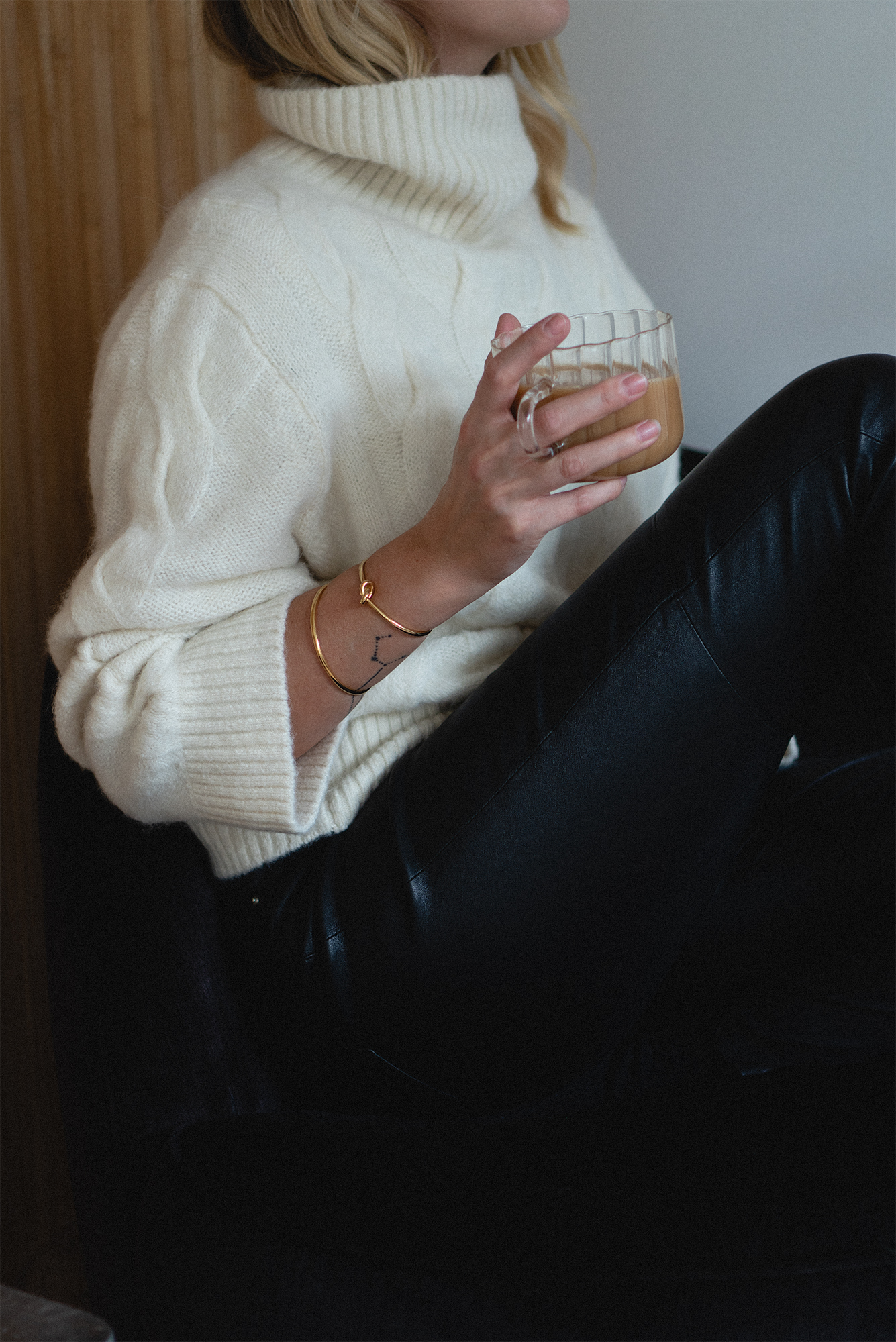 cream chuky cable knit jumper, glass tea cup, leather trousers, cosy winter outfit