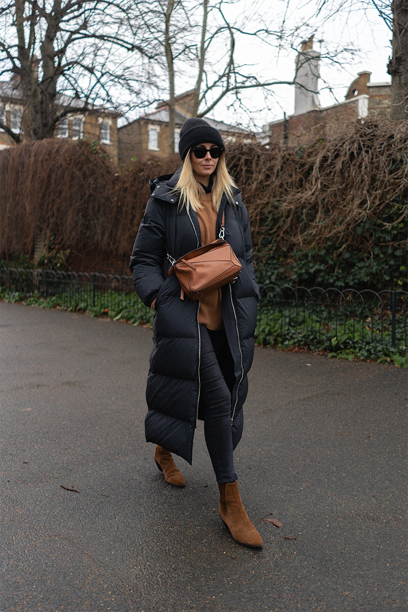 Emma Hill style. Black long puffa coat, black beanie hat, tan jumper, black skinny jeans, tan suede Saint Laurent ankle boots, Tan leather Loewe Puzzle bag. Casual Winter outfit