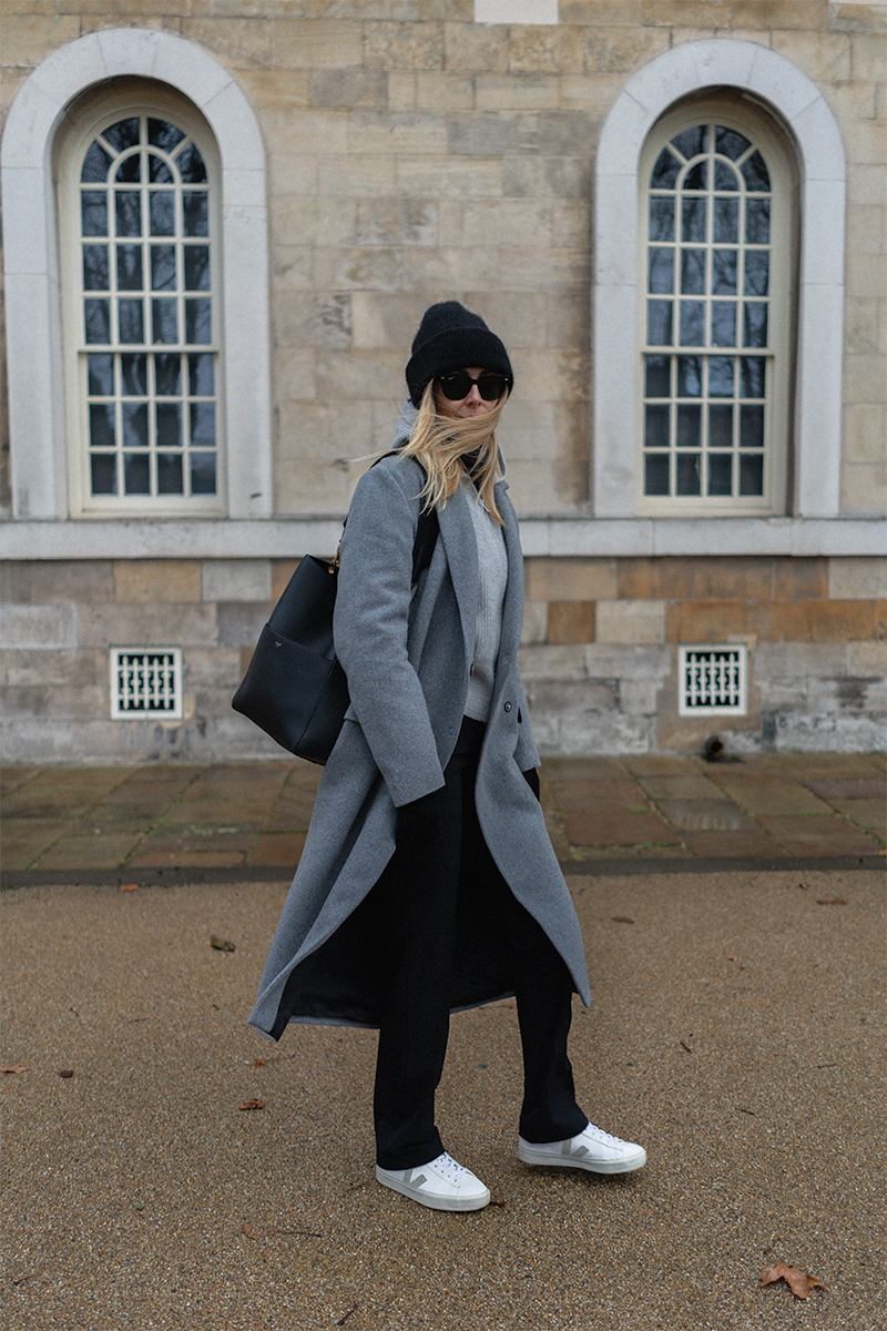 Emma Hill style. Long grey coat, Black Celine Seau Sangle bag, grey cashmere hoodie, black tailored trousers, Veja Campo trainers, black ribbed beanie hat. Casual Winter outfit