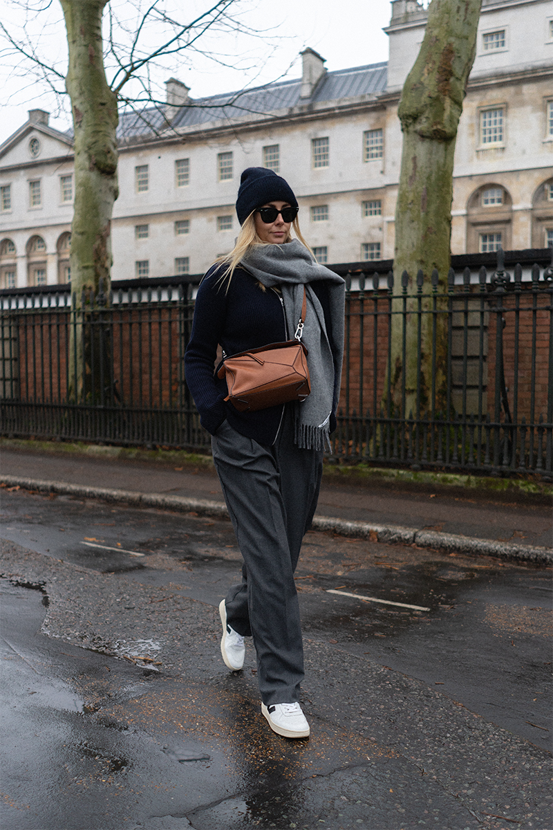 Emma Hill style. Navy ribbed knitted zip cardigan, tan leather Loewe Puzzle bag, navy blue beanie hat, grey Acne scarf, Veja V-10 white leather trainers, grey wide leg tailored trousers. Casual Winter outfit