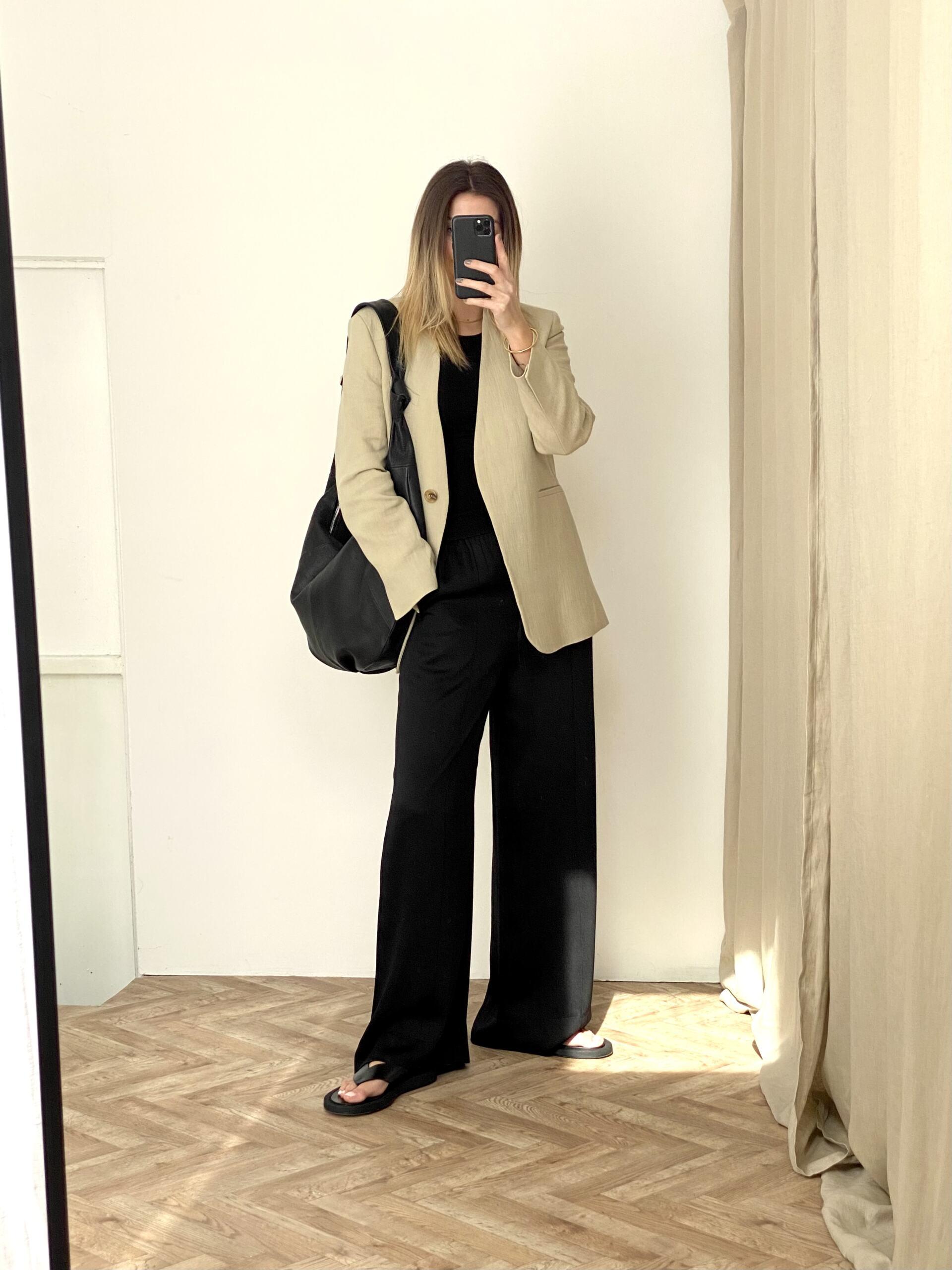 Emma Hill wears beige linen blazer, black wide leg trousers, thong flip flop black leather sandals, chic Spring outfit